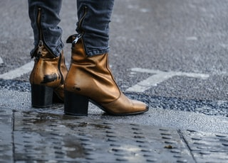 person in brown leather boots standing on gray concrete road during daytime