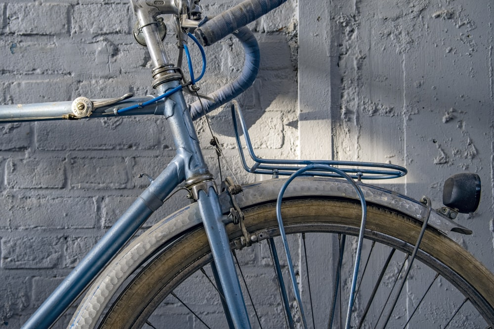 blue and silver bicycle leaning on blue metal fence