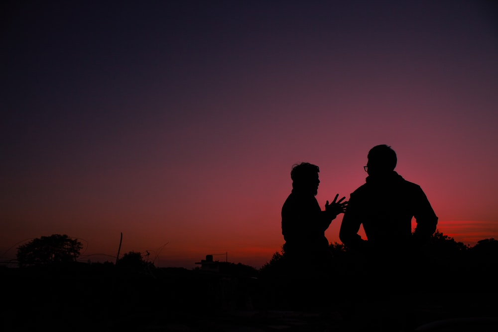 silhouette of 2 men sitting on ground during sunset