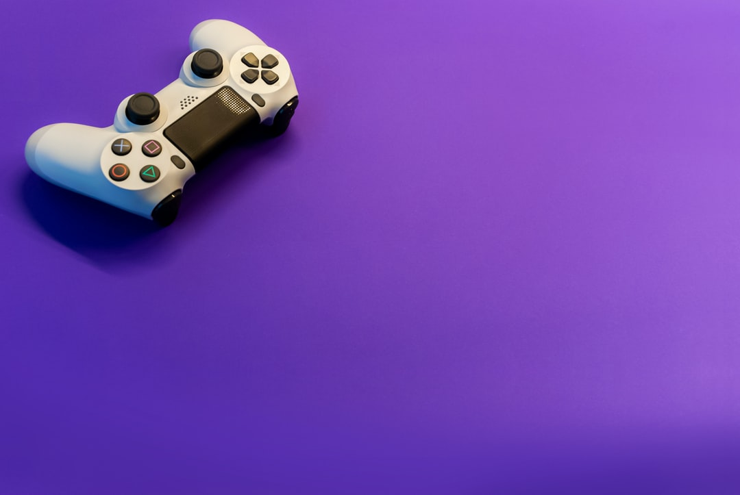 A playstation remote control on a purple background
