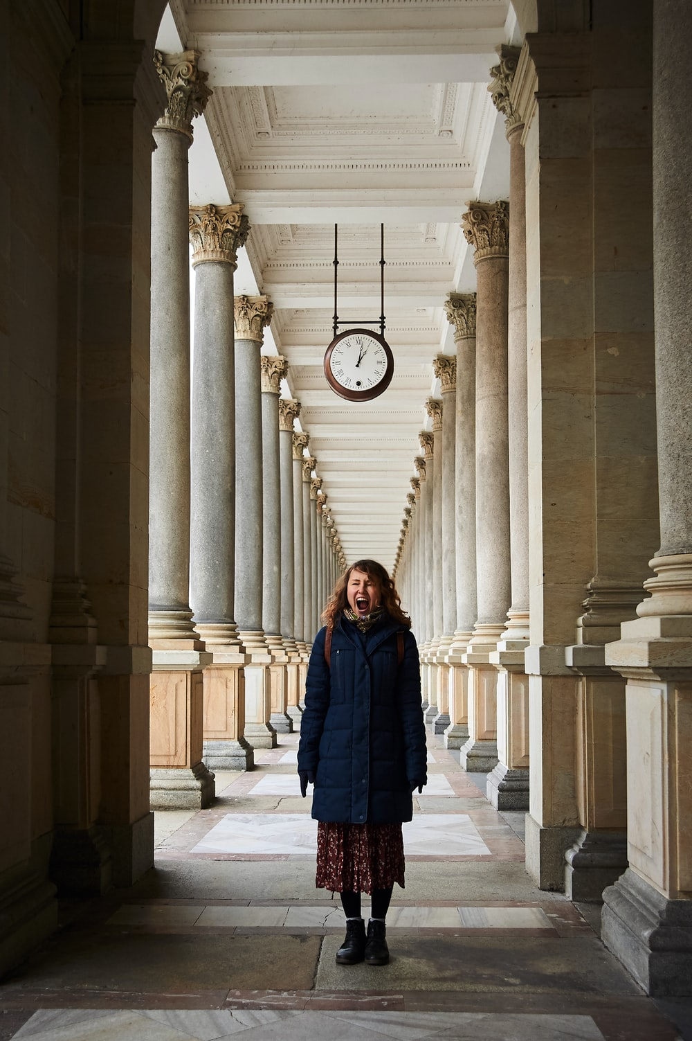 woman in blue coat standing near white concrete pillar during daytime