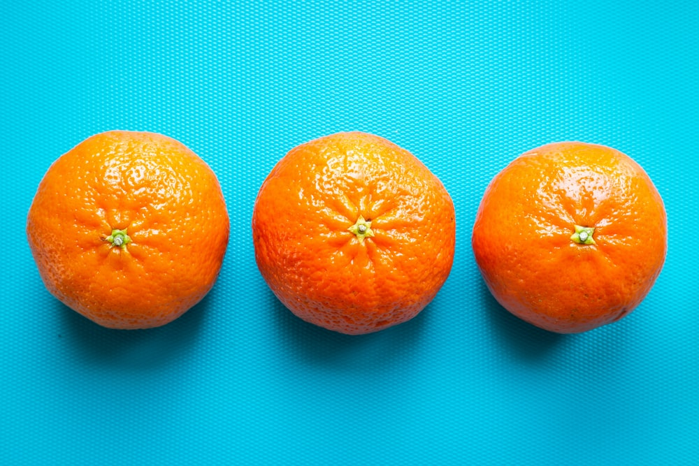 2 orange fruit on blue and white polka dot textile