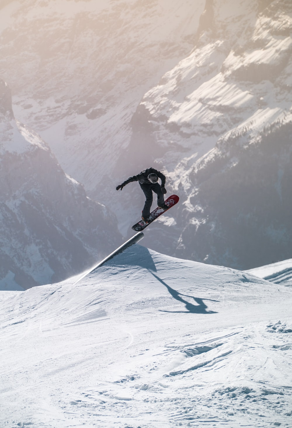 man in red jacket and black pants riding on ski blades on snow covered mountain during