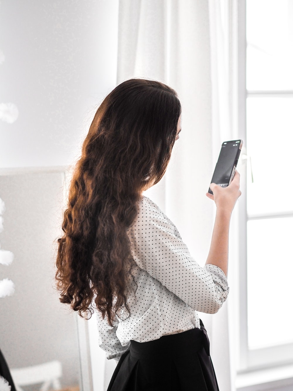 woman in white and black long sleeve shirt holding silver smartphone