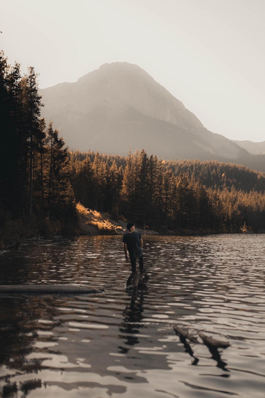 man in black jacket standing on river during daytime