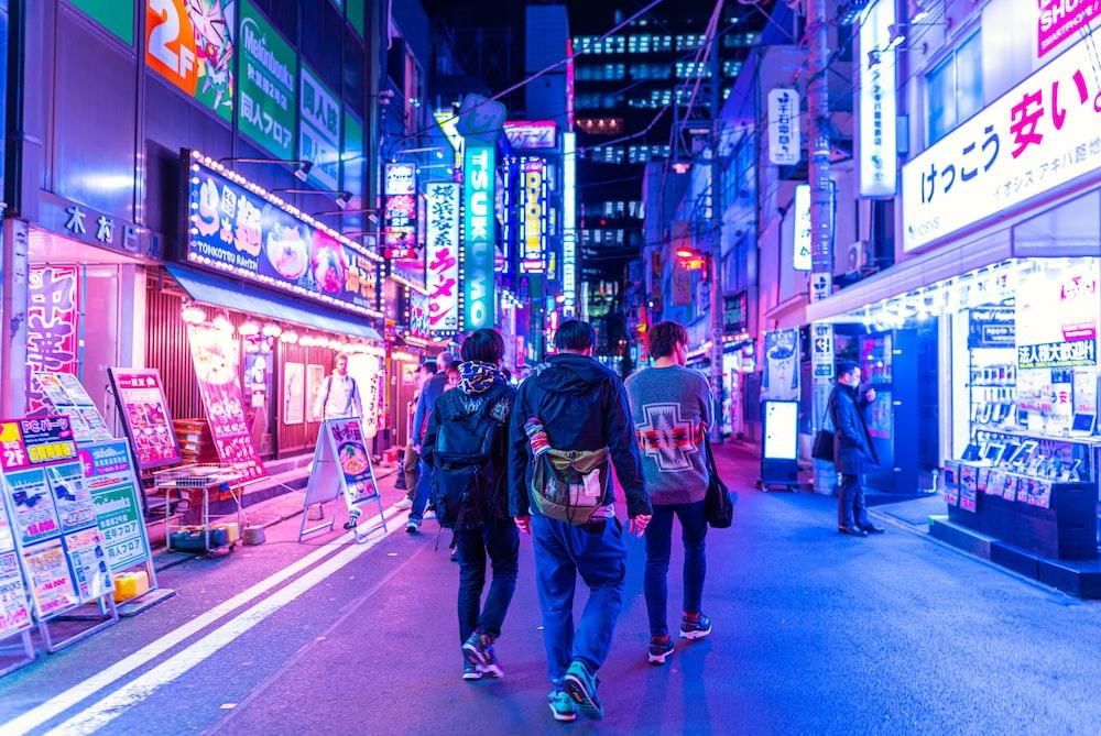 man in blue denim jeans walking on street during nighttime