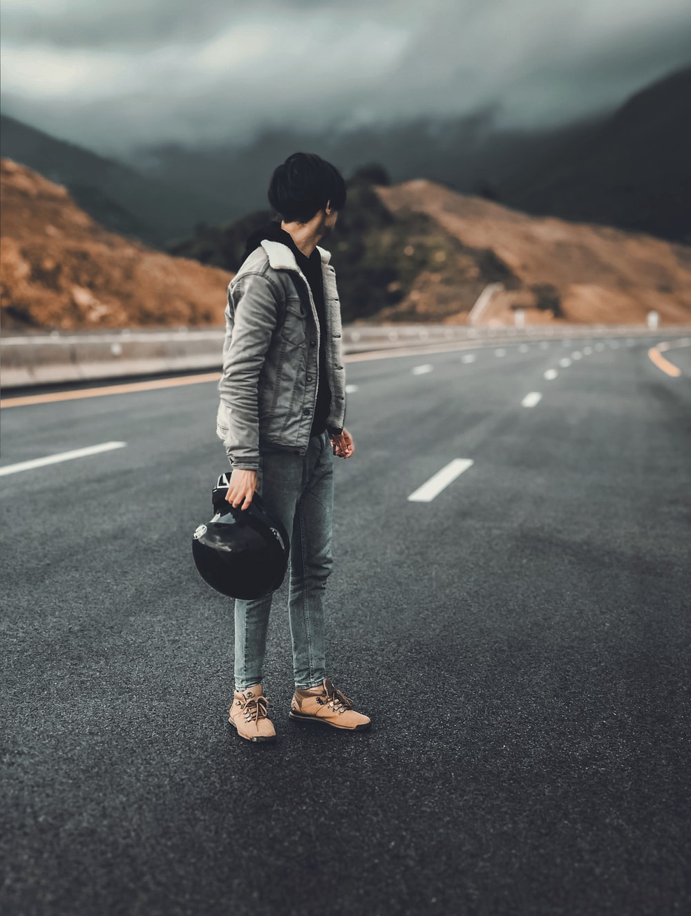 man in white jacket and black pants holding black hat standing on road during daytime