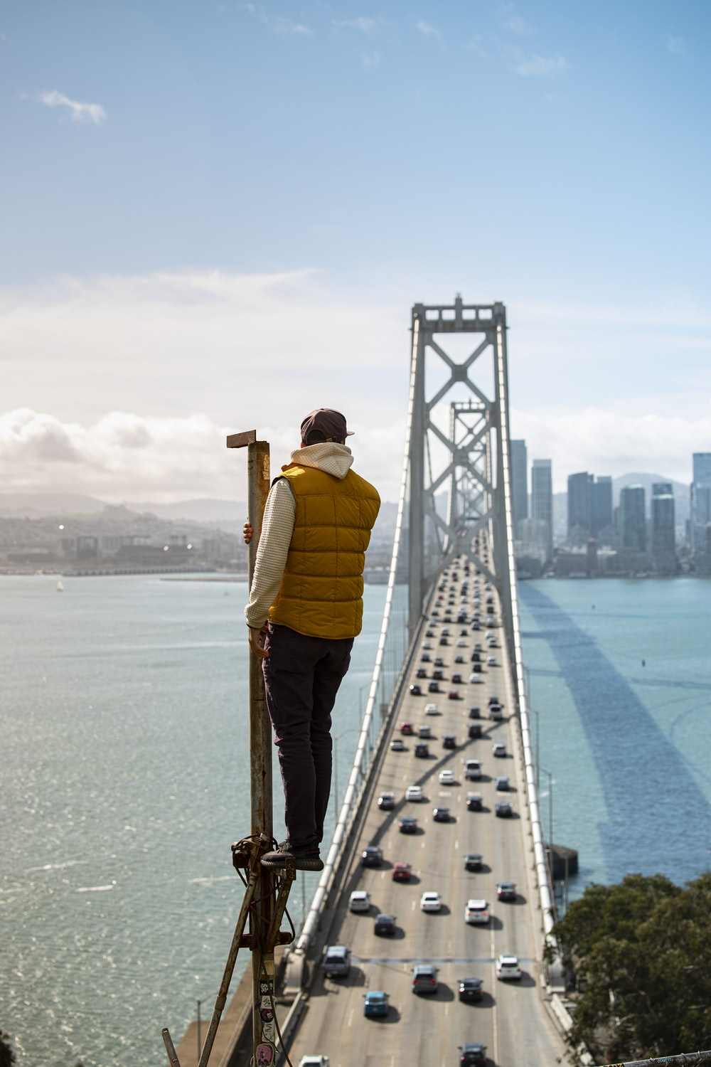 man in yellow jacket and brown pants standing on bridge during daytime