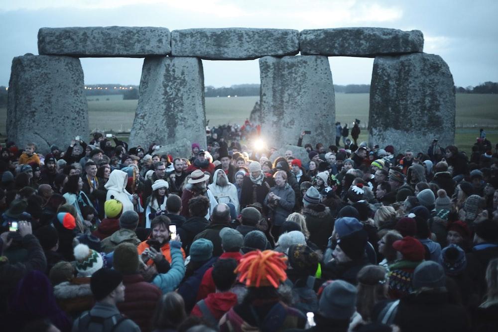 people gathering near gray concrete pillar during daytime