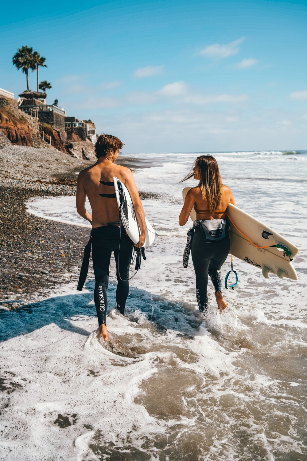 woman in white tank top and black pants holding white surfboard standing on beach during daytime