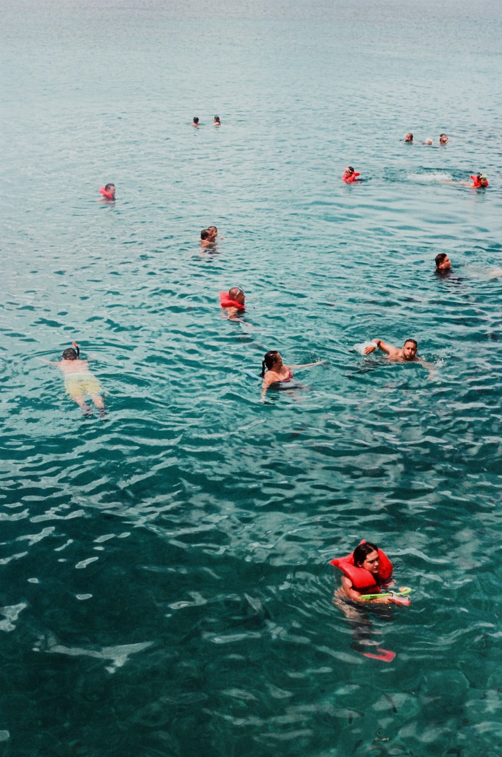 group of people swimming on water during daytime