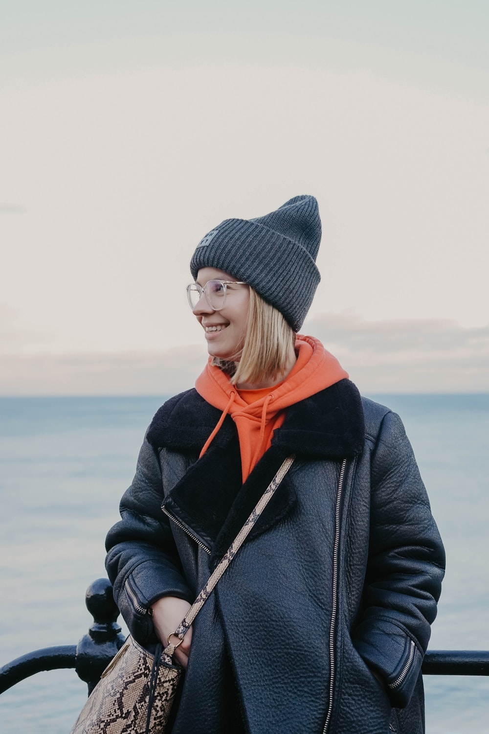 woman in black knit cap and gray coat standing on beach during daytime
