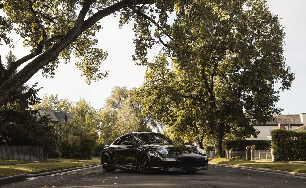 black car on road near trees during daytime