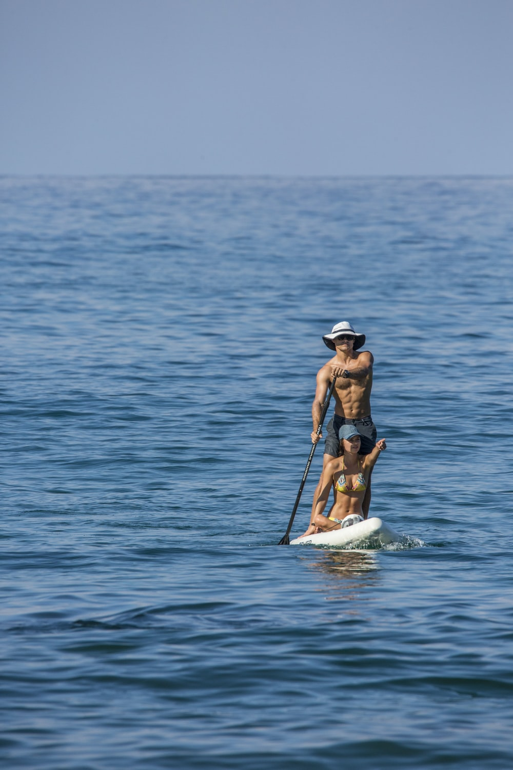 woman in blue bikini on white surfboard in the middle of sea during daytime