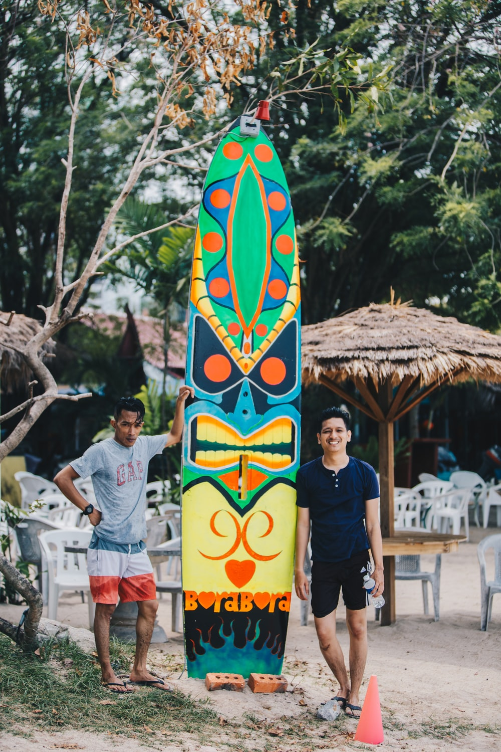 man in black crew neck t-shirt standing beside blue and yellow surfboard