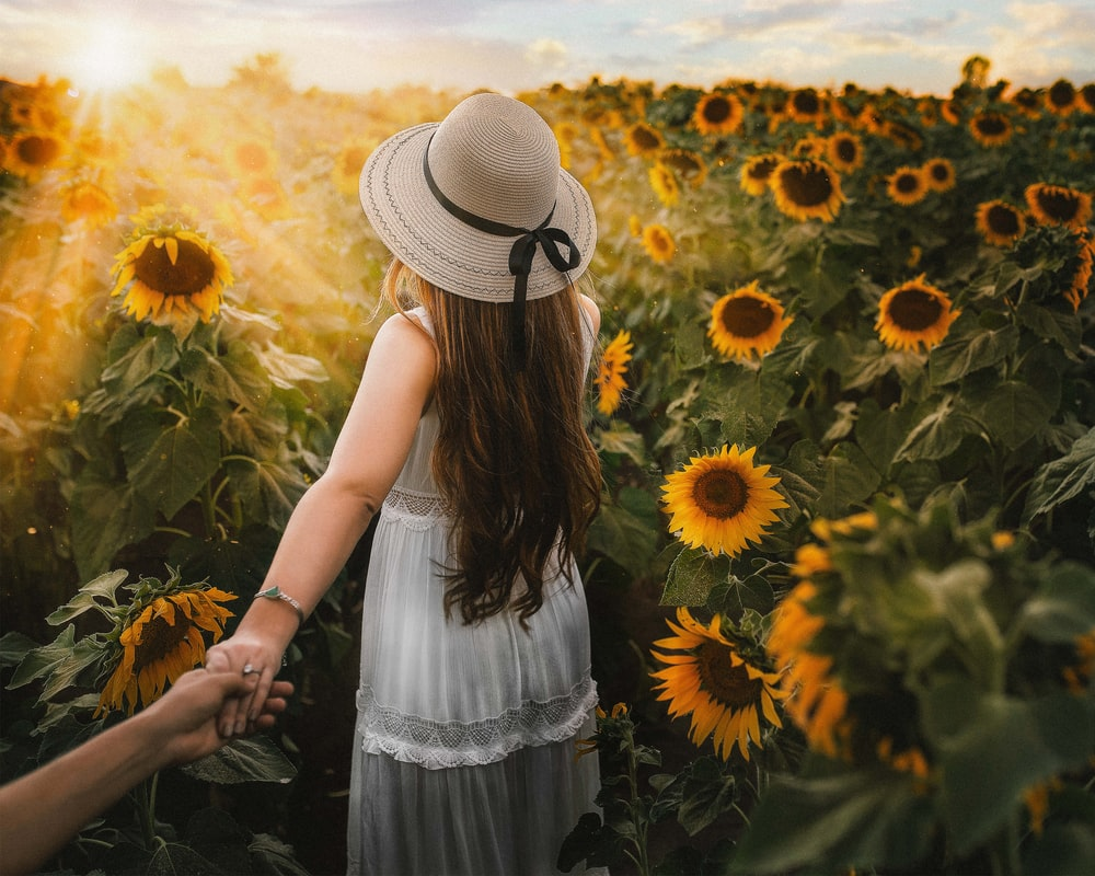 woman in white dress standing on sunflower field during daytime