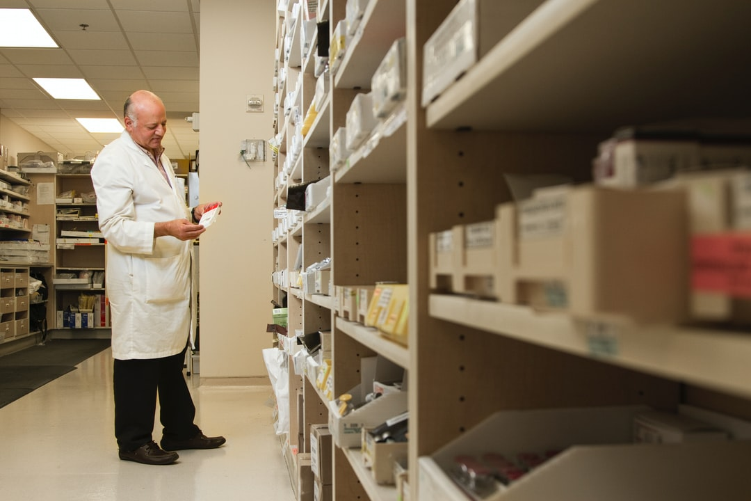 A Male Pharmacist Is Examining A Drug From A the Pharmacy Inventory. - unsplash