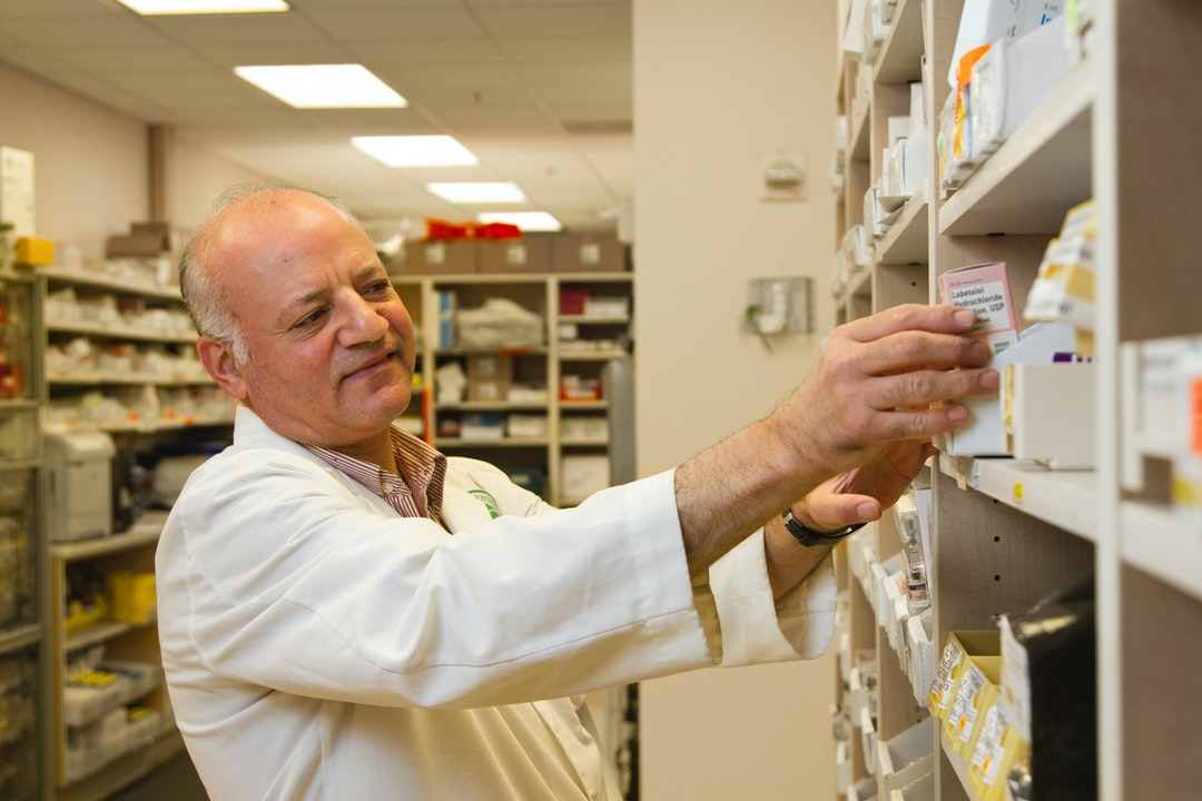 """""""A male pharmacist is selecting a drug from a display case in a pharmacy."""""""