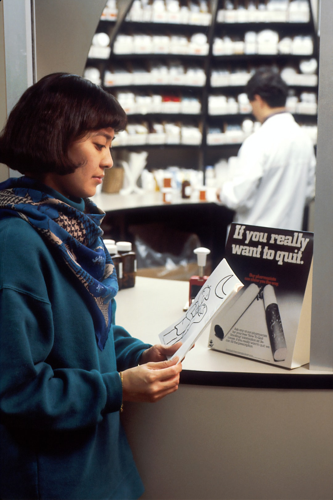An Asian female reading a booklet at a pharmacy counter while a male pharmacist works in the background.