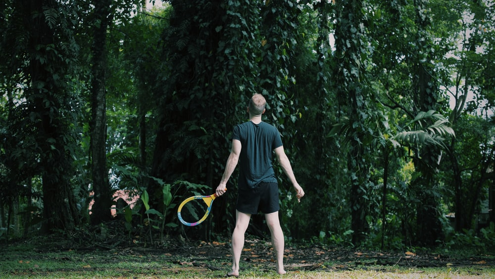 man in black crew neck t-shirt and black shorts playing with yellow and green basketball