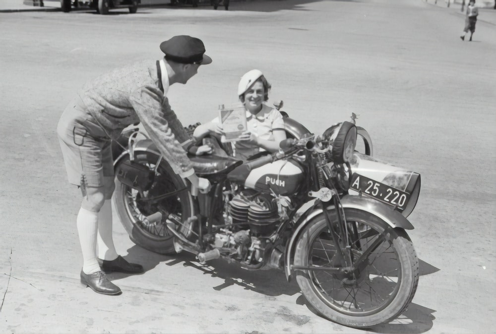 man in gray jacket and black cap riding black motorcycle