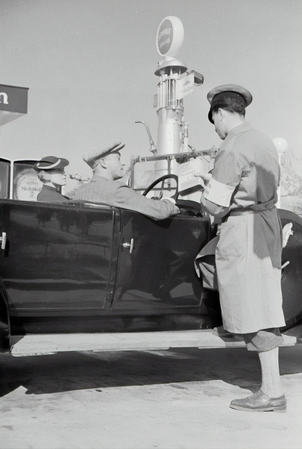 man in white uniform standing beside black car