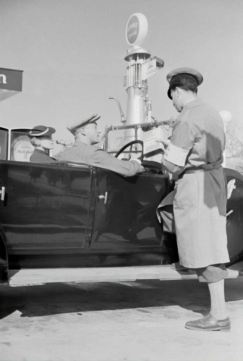 man in white uniform standing beside black car