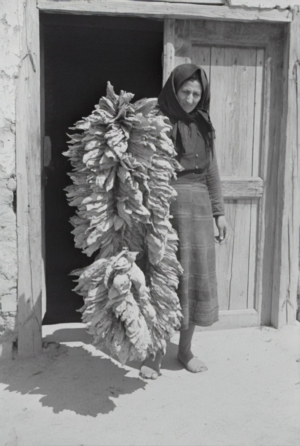 woman in black jacket and white skirt standing beside wooden door