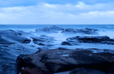 rocky shore under cloudy sky during daytime tempest teams background
