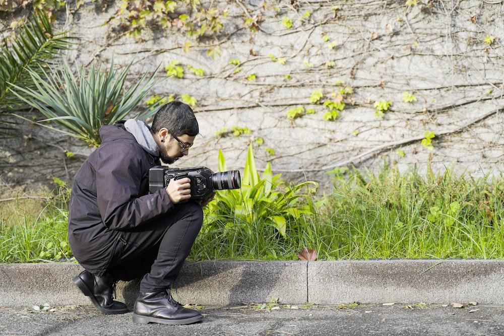 man in black jacket and black pants holding black dslr camera