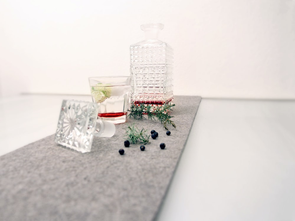 clear glass bottle with red liquid on white table