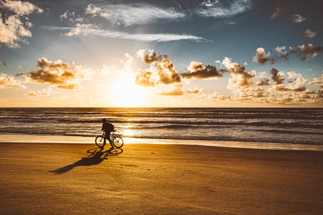 Silhouette of A Man Riding His Bike At the Beach - unsplash