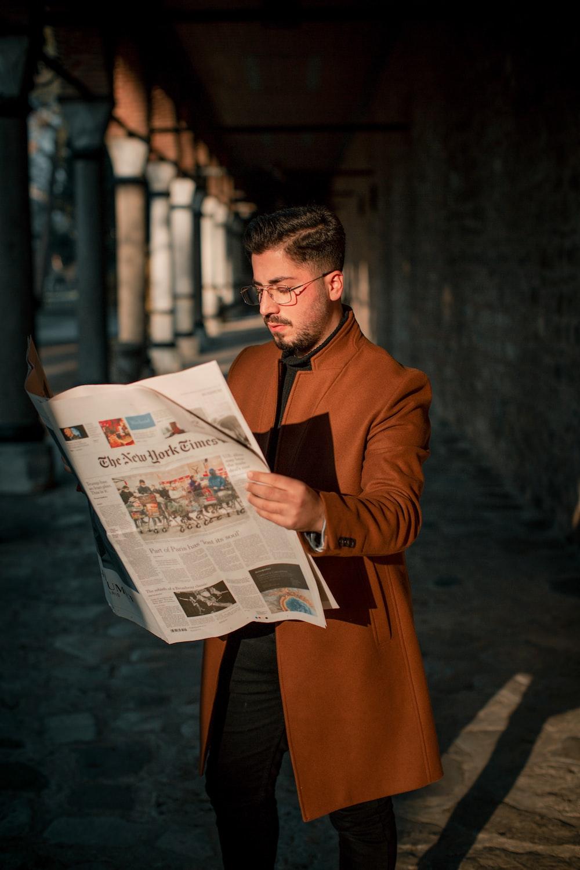 man in brown coat reading newspaper