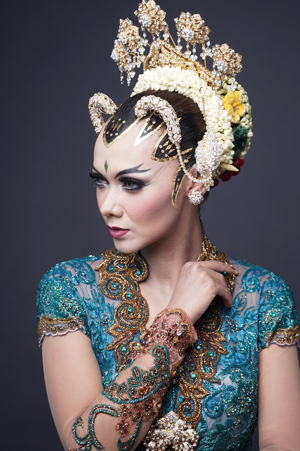 woman in blue and brown floral dress wearing gold crown