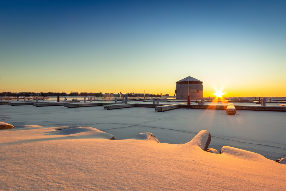 brown wooden house on snow covered ground during sunset