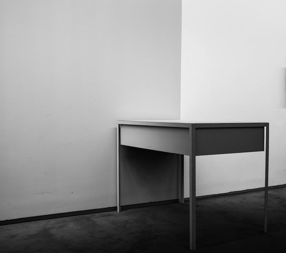 white wooden desk beside white wall