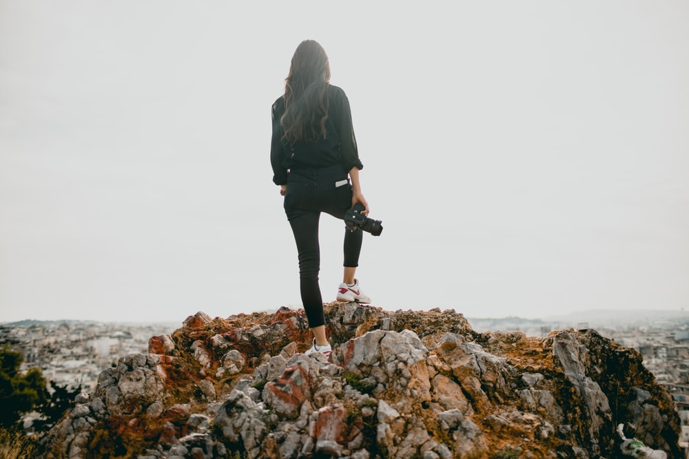 woman in black jacket standing on brown rocky mountain during daytime