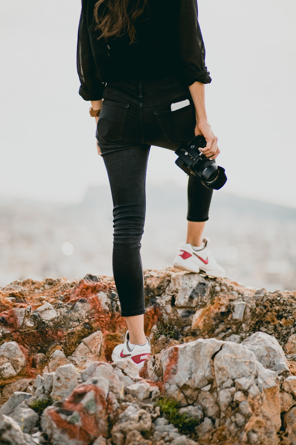 woman in black shirt and black pants holding black dslr camera