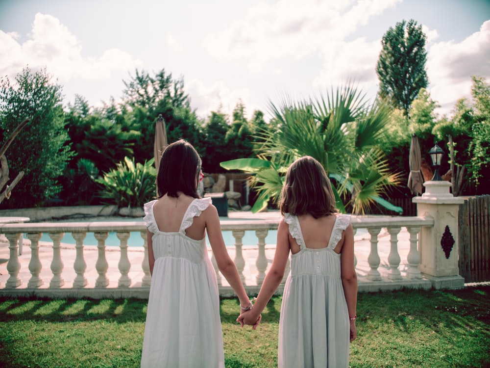 2 girls in white dresses standing on green grass field during daytime