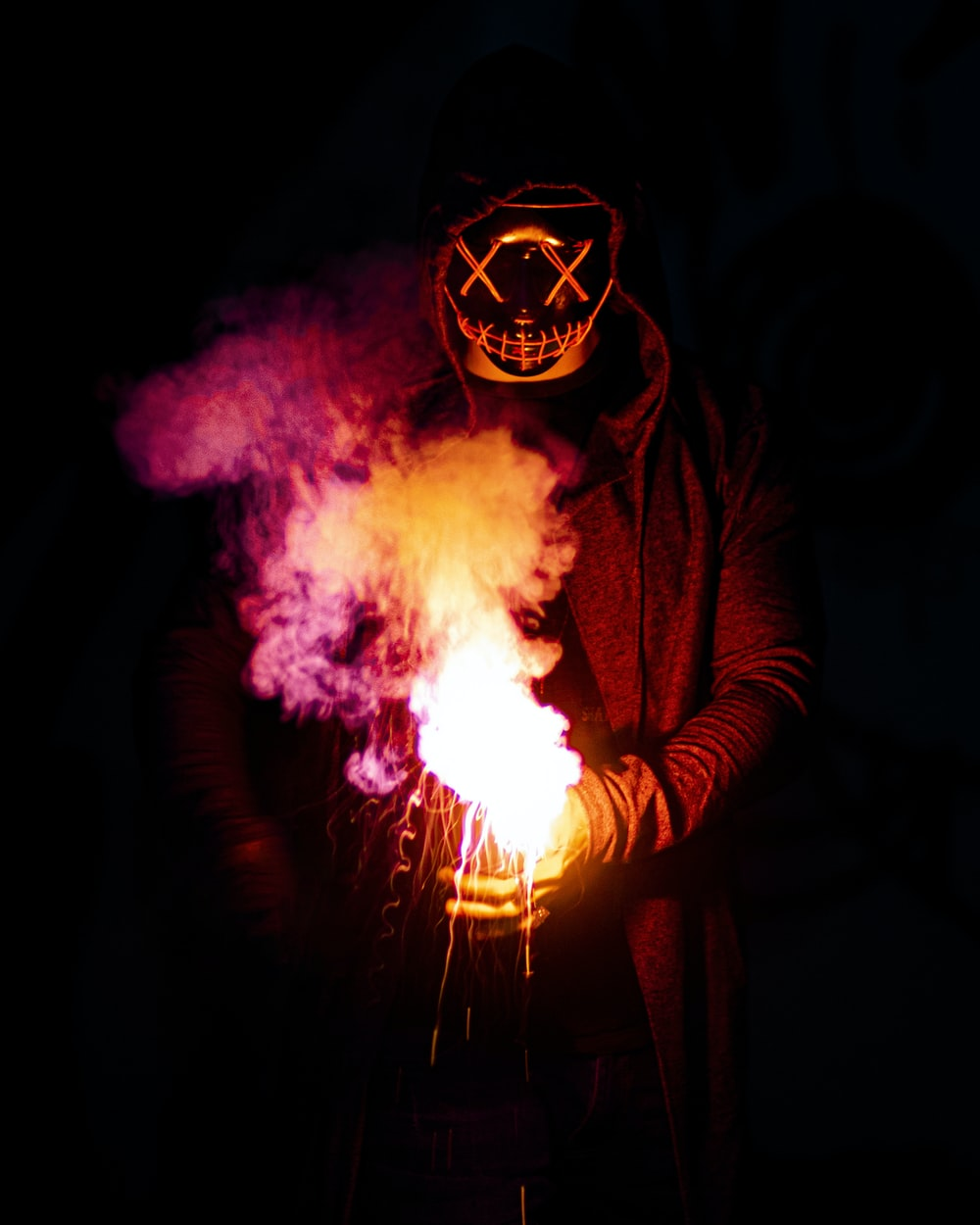 person in black mask holding purple and pink smoke