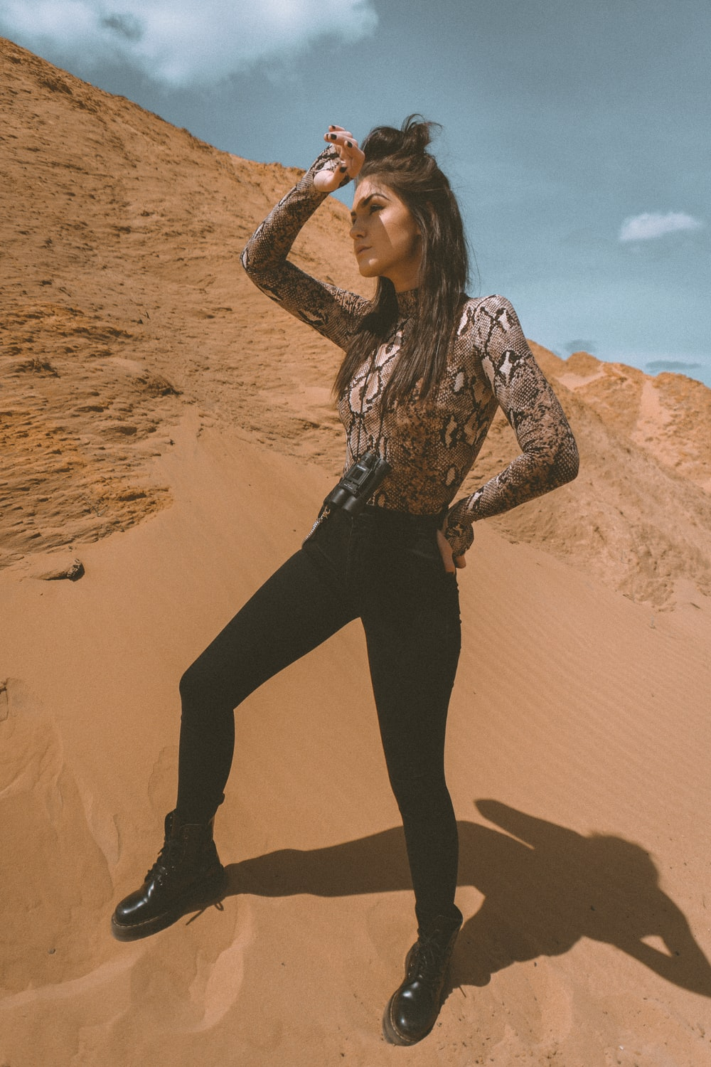 woman in black pants and brown and white long sleeve shirt on brown sand during daytime