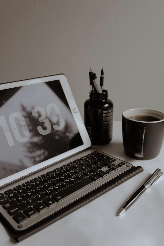 macbook air beside black pen and black ceramic mug