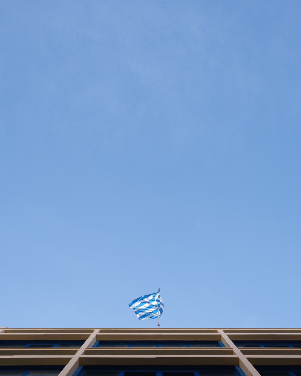 blue and white striped flag on pole under blue sky during daytime