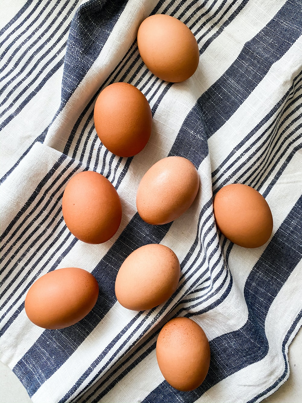 brown egg on white and blue stripe textile