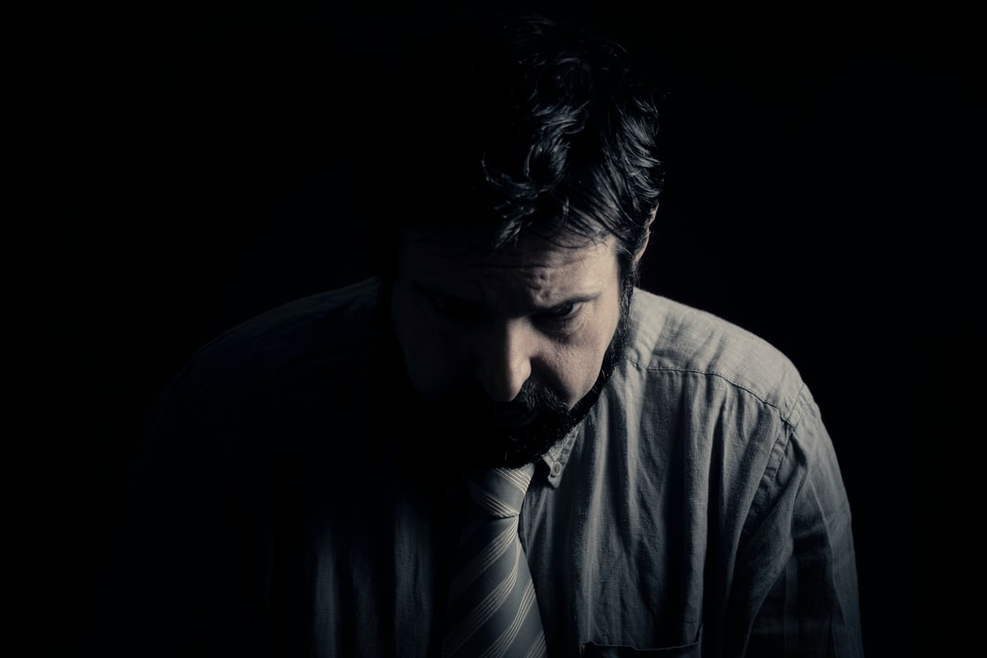 A sad, depressed man, sitting alone in the darkness. Bad feelings, human emotions, the face of depression, having complex thoughts and tough decisions to take. This is a better version of my 1st upload.