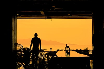 Bo silhouette of man standing on dock during sunset
