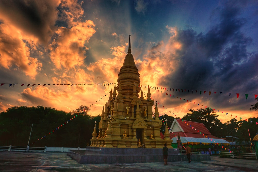 gold and black temple under cloudy sky