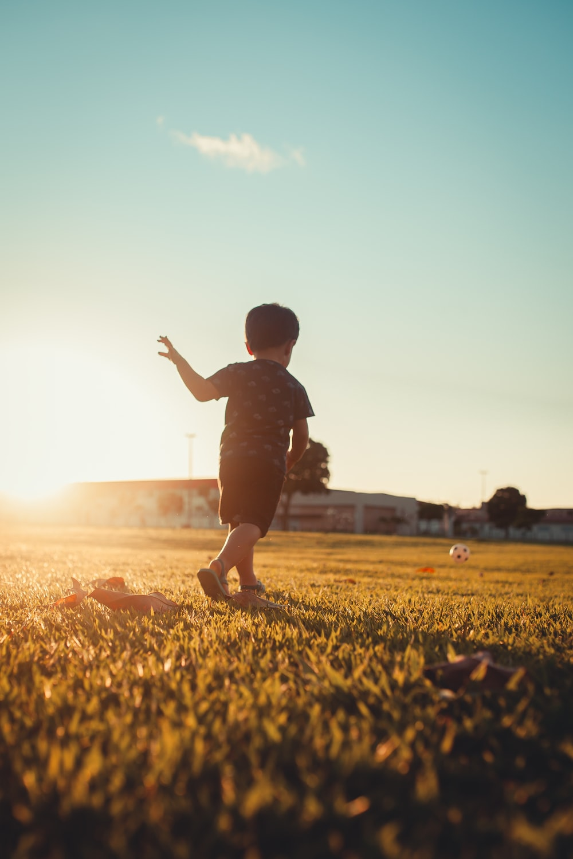 boy in black shirt running on green grass field during daytime