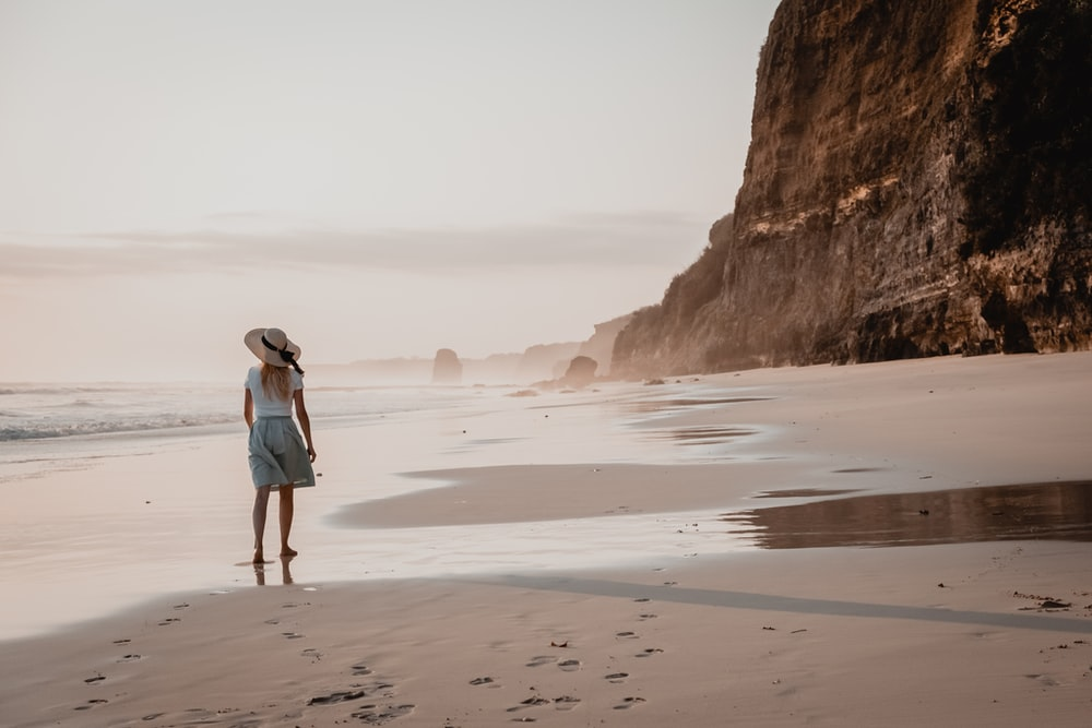 woman in white shirt and blue denim shorts walking on beach during daytime
