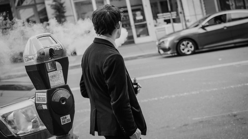 man in black jacket standing on road